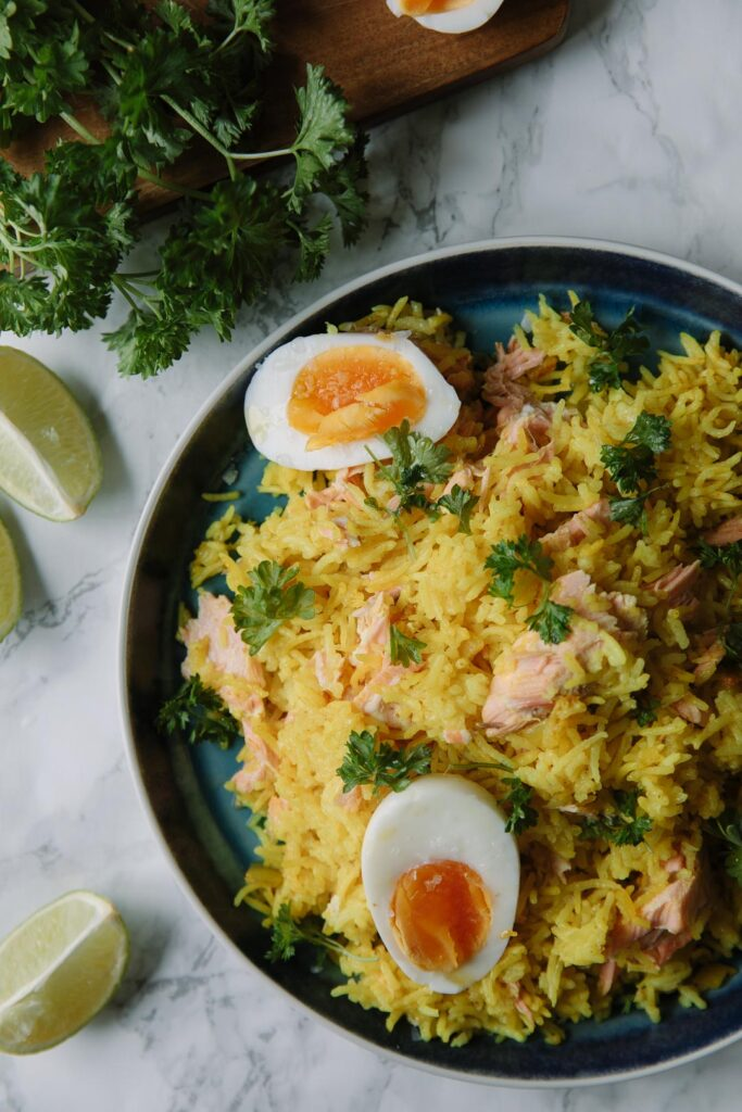 Yellow rice with poached salmon, boiled eggs and parsley