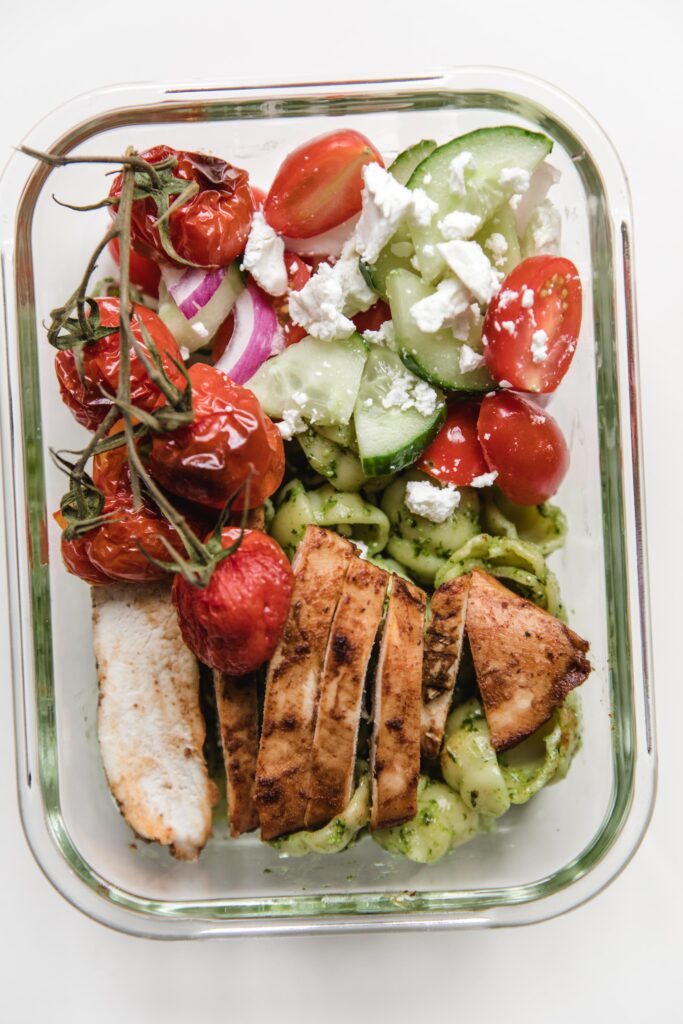 Lunch box-pesto pasta, marinated chicken with greek salad and baked tomatoes