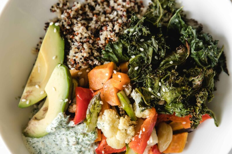Quinoa, baked vegetables and healthy green goddess dressing buddha bowl